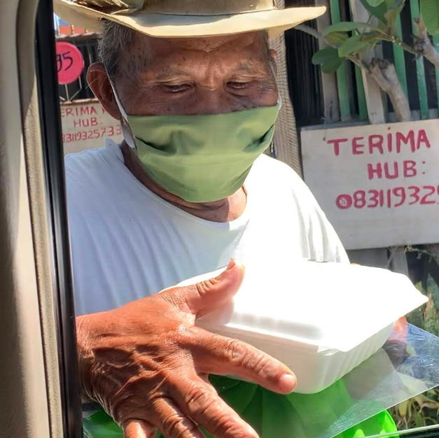 street vendor receiving meal box and Rp. 100.000 food bag