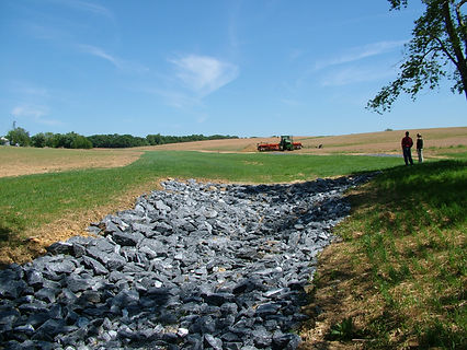 Waerway outlet on a farm, lined with large stones