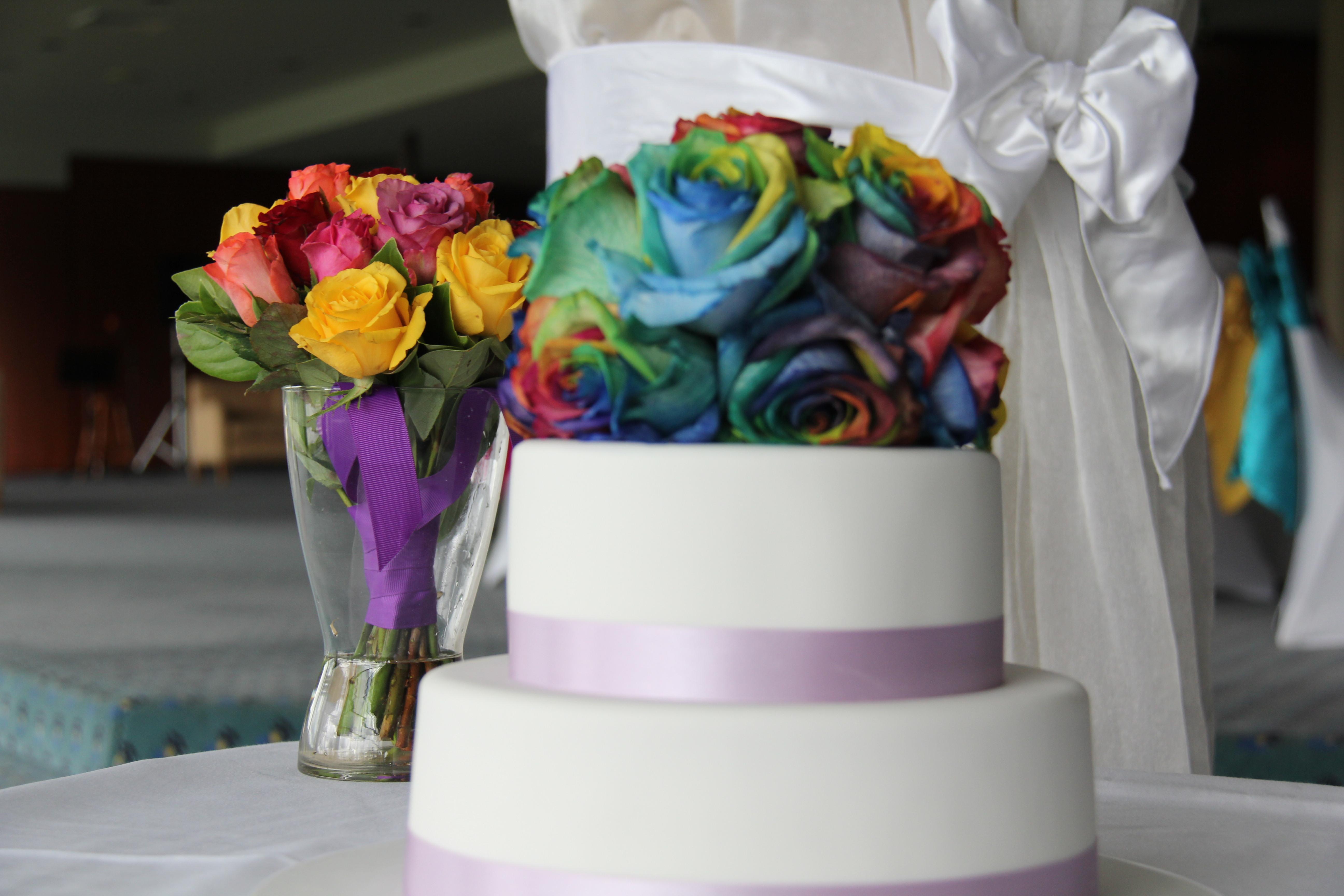 rainbow roses atop a rainbow cake