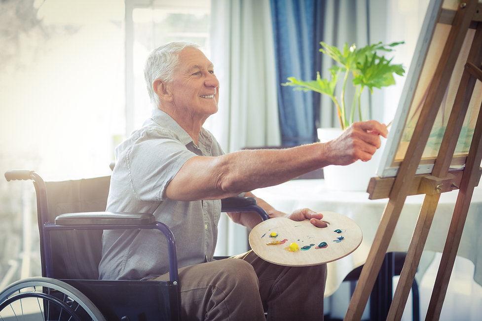 Happy senior man painting at home.jpg