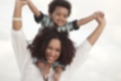 Woman holding her son on her shoulders.j