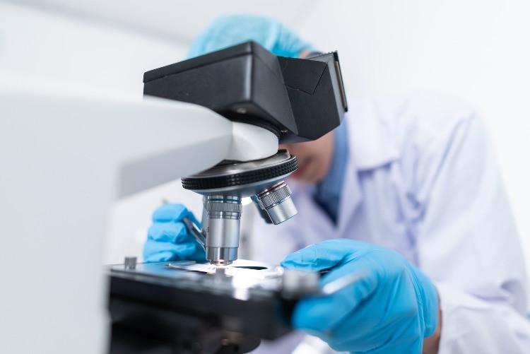 scienziato con guanti blu e camice bianco che utilizza il microscopio