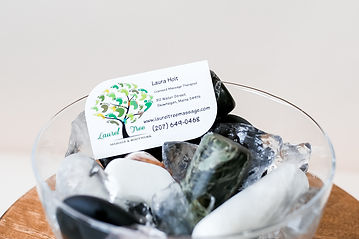 Hot and cold stones sitting in ice used for treatments in massage with our business card