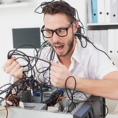 Angry computer engineer pulling wires in