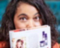 Lady peeps over magazine