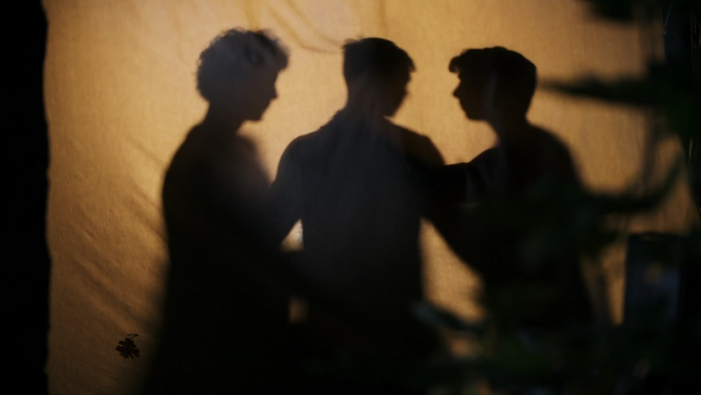 shadows of three men against a tent in the TV series Shadowlands where polyamory is explored.