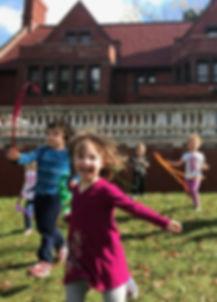 preschool class dancing  with ribbon wands outside