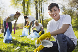 Dirty park. Positive male volunteer grinning to camera while collecting litter.jpg