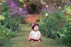 little irl sitting between flowers