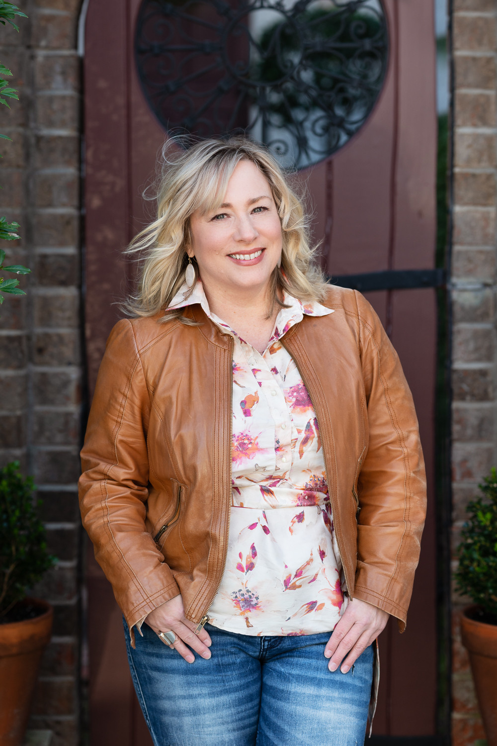 headshot of woman in leather jacket, smiling and happy, downtown Southern Pines