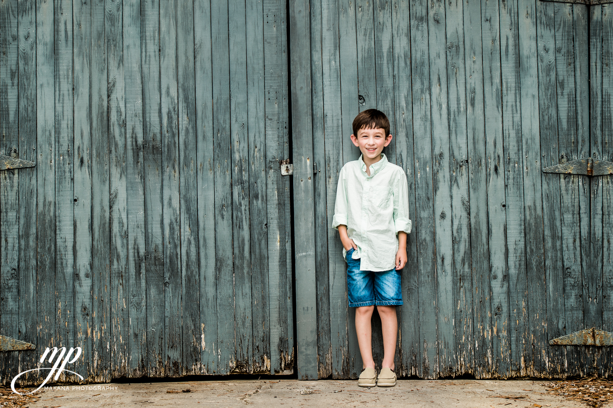 boy leaning on vintage shed