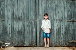 boy leaning on vintage shed