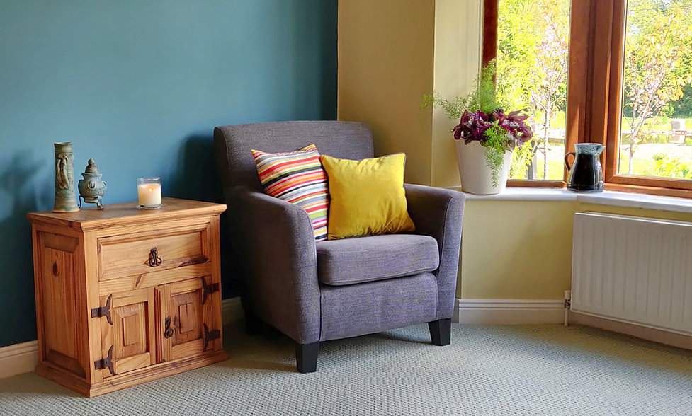 The therapy room, an inviting armchair with cushions in a warm room with a view of a garden outside