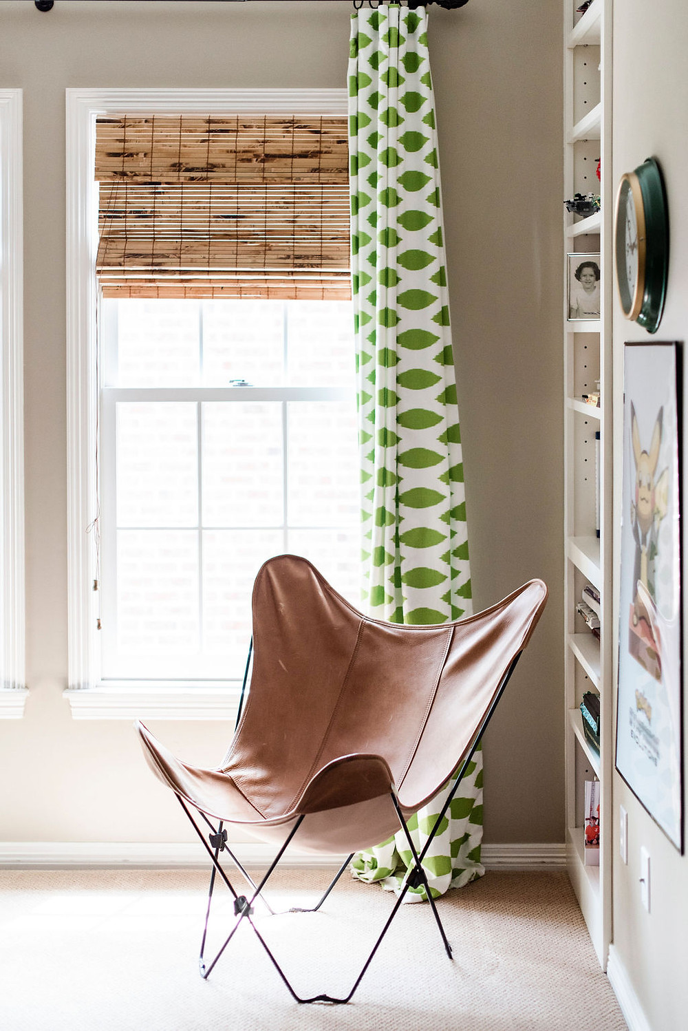 Tween bedroom project in West University, Texas  by Houston interior design firm Nancy Lane Interiors featuring warm greige paint as a backdrop with fun colorful curtains and a leather butterfly lounge chair.