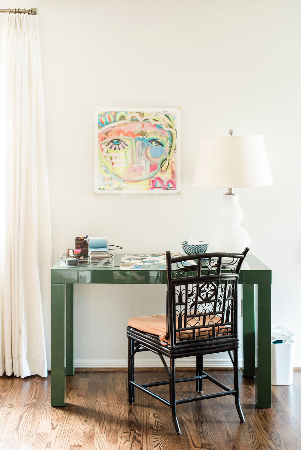 Design studio office of Houston based interior design firm Nancy Lane Interiors featuring green acrylic desk and colorful artwork by Windy O'Connor.