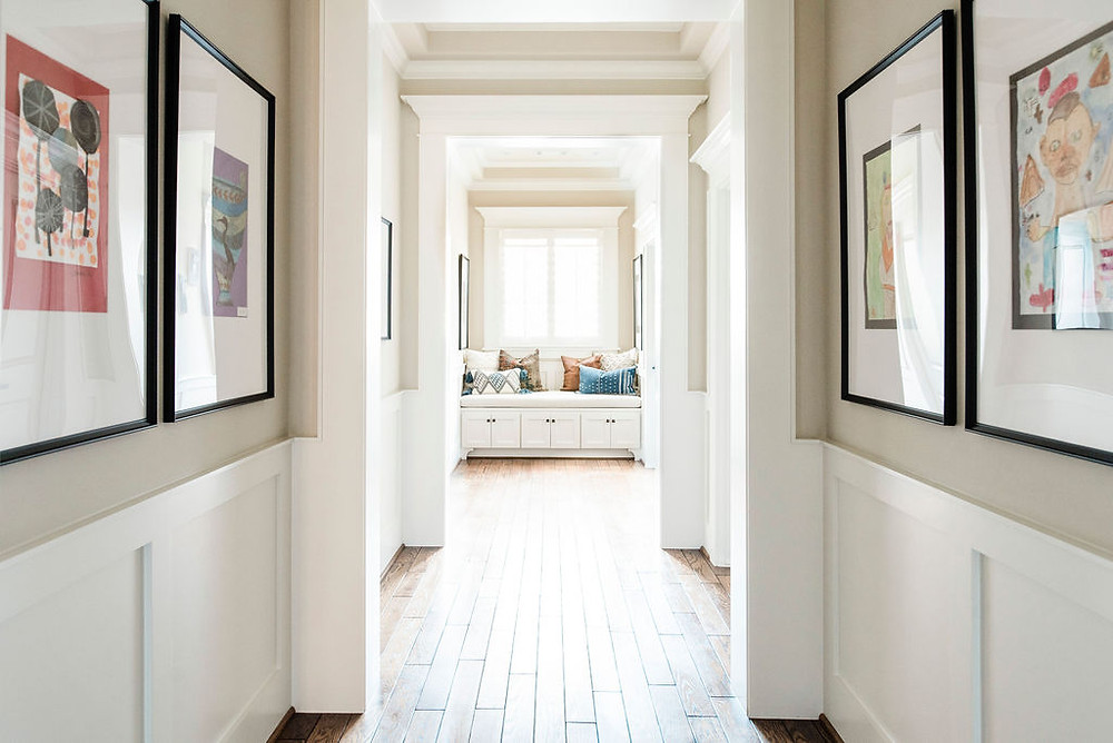 Transitional hallway art gallery featuring our clients' kids treasured art pieces by Houston residential design firm Nancy Lane Interiors.