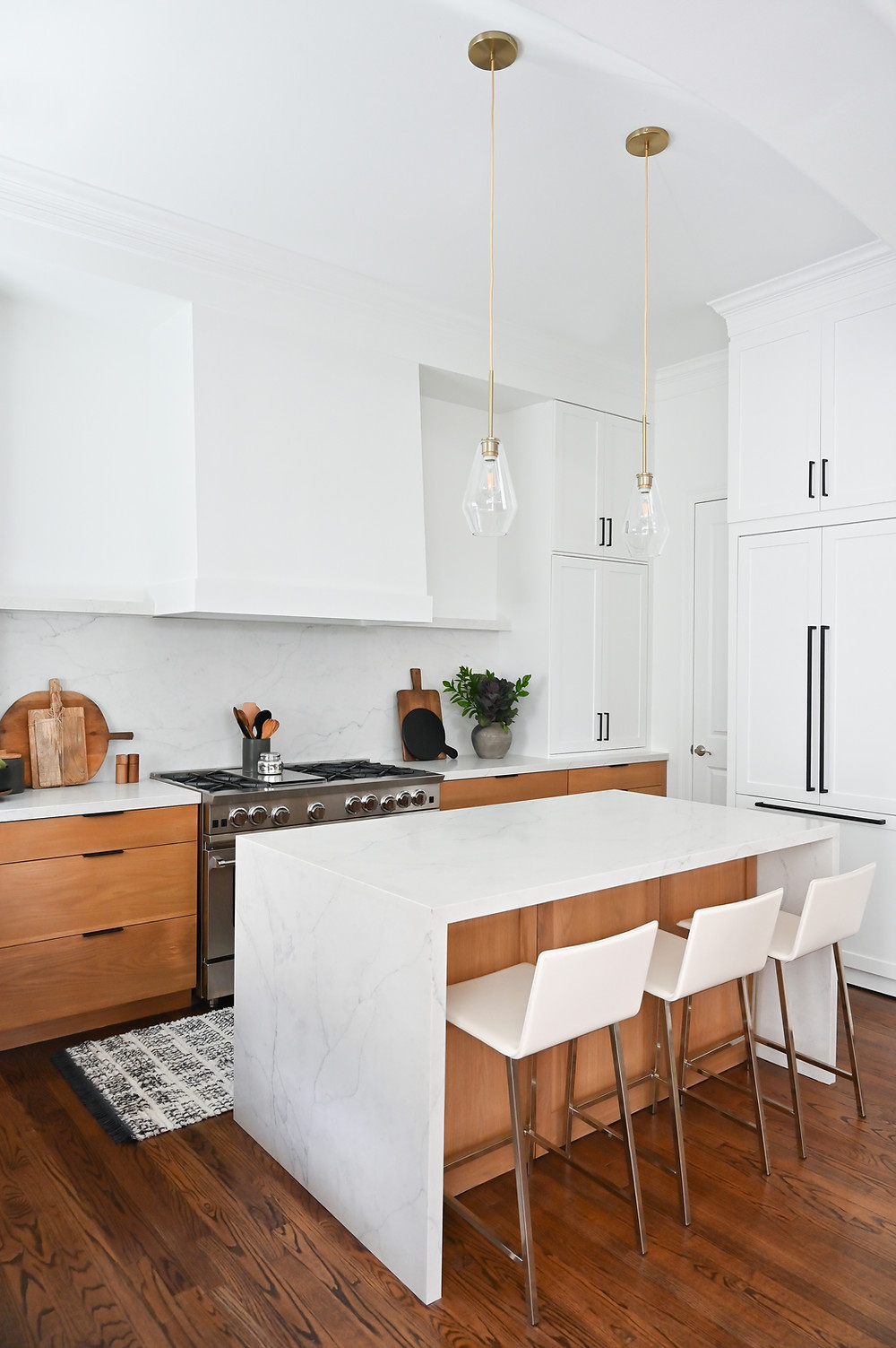 A Modern Minimalist Kitchen featuring waterfall countertop island by Houston interior design firm Nancy Lane Interiors.