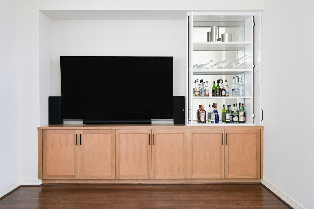 A Modern Minimalist Kitchen and living room featuring custom built in bar and entertainment area by Houston interior design firm Nancy Lane Interiors.