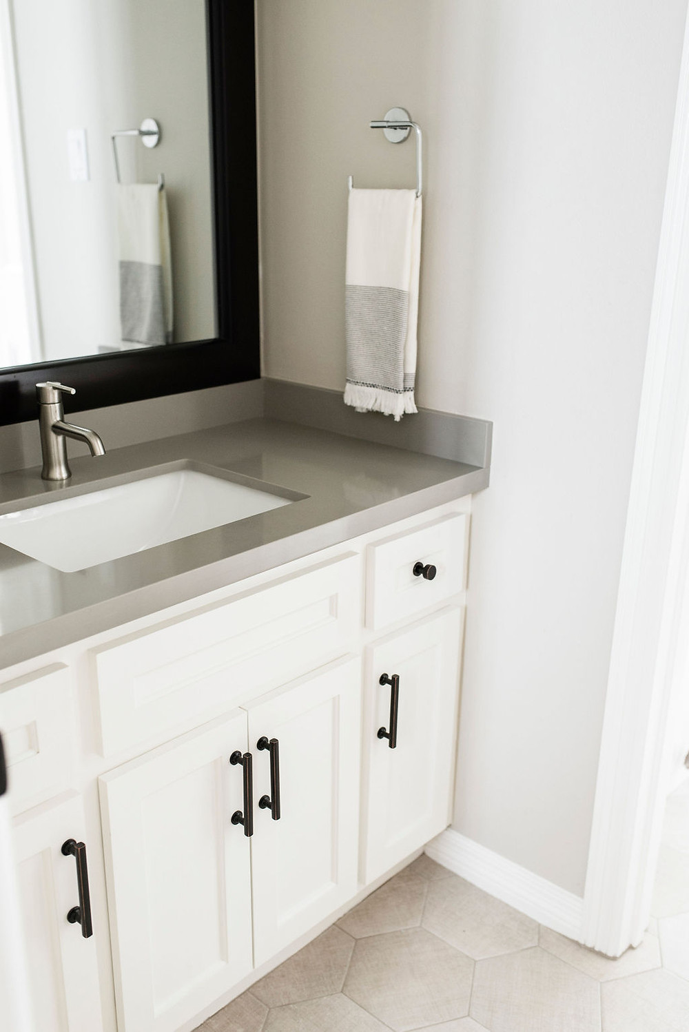 Modern transitional secondary bathroom project reveal featuring hexagonal floor tiles   by Houston interior design firm Nancy Lane Interiors.