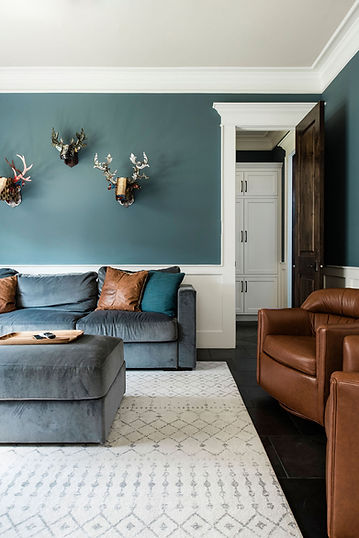 This mixed use room morphs from a kids' hang out spot to a guest room in the blink of an eye. Take a look around and see if you can guess how? If you say I spy the murphy bed behind the pair of gorgeous leather chairs then you win the prize! Photos by Madeline Harper Photography