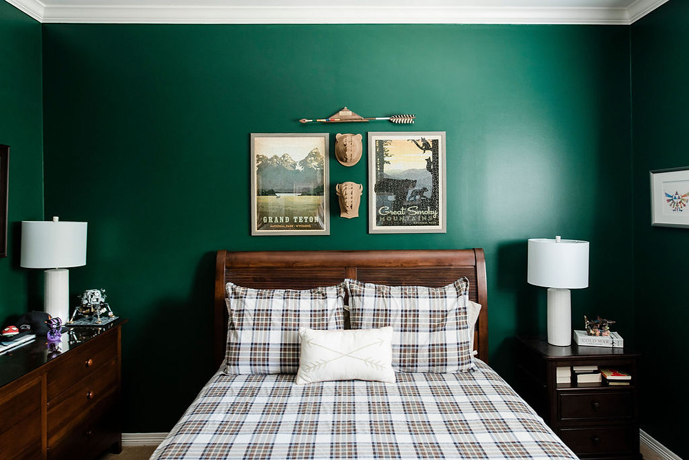 Teen boys bedroom featuring outdoorsman theme in deep forest green by Houston residential design firm Nancy Lane Interiors