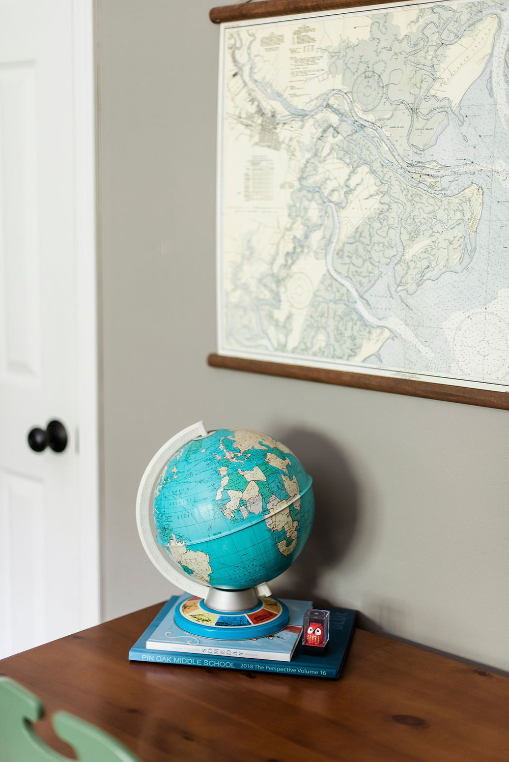 Boys bedroom featuring a mix of warm woods and antique maps by  by Houston interior design firm Nancy Lane Interiors.