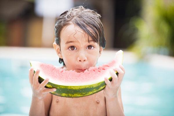 Jeune garçon Tahitien qui mange une pastèque