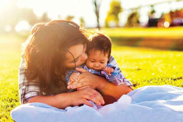 Maman et son bébé sur une pelouse - Le centre de Protection maternelle et infantile (CCSPMI).