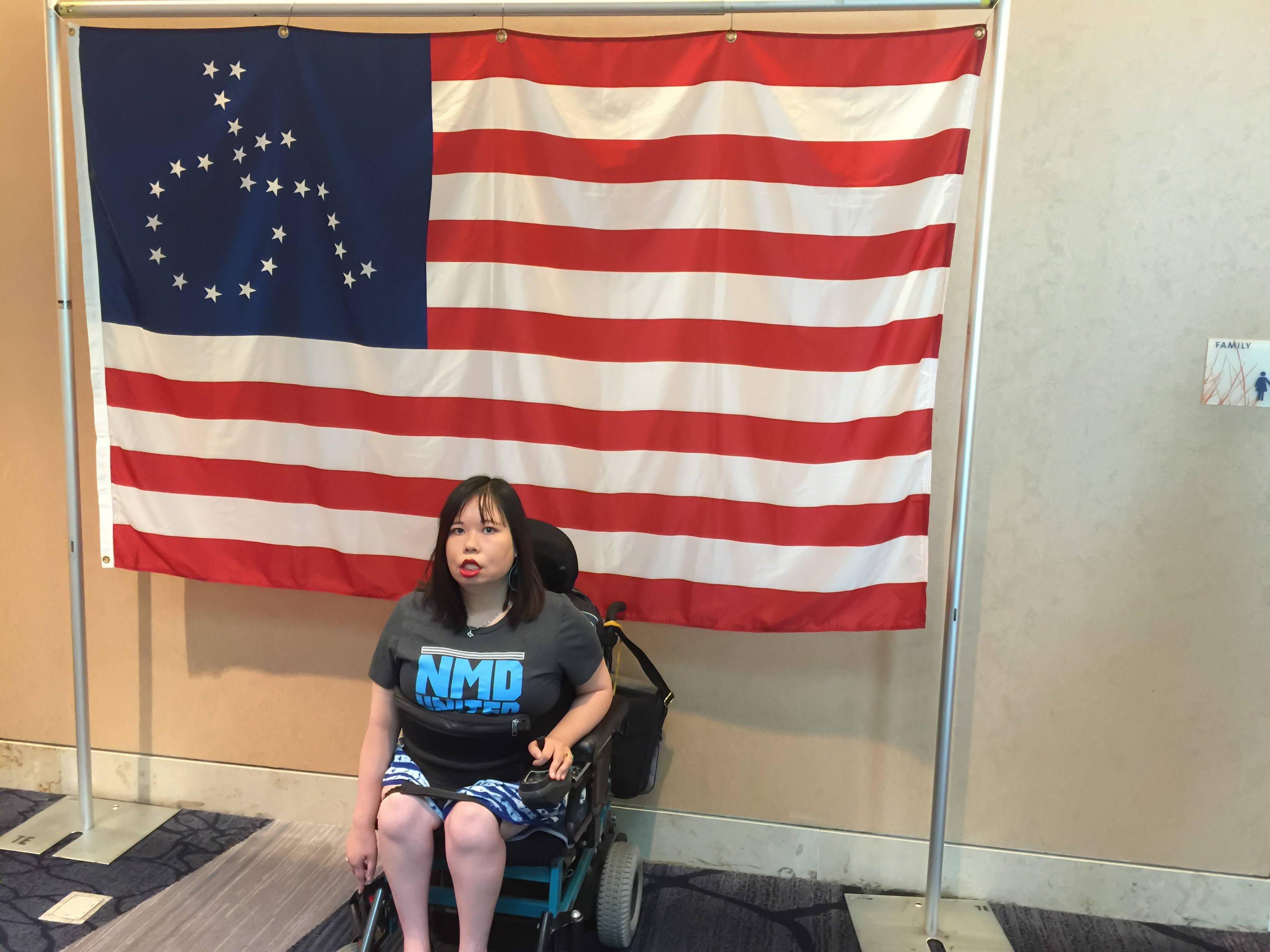 Woman sitting in her powerwheelchair in front of an ADAPT flag, wearing a NMD United shirt.