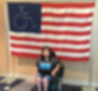 A woman with shoulder length, dark hair is sitting in a power wheelchair. She is front of a very large flag, which resembles the United States red and white stripes with blue background and white stars in the upper left corner. The stars are in the shape of the international symbol for disability, a side view of a stick figure person sitting in a wheelchair. The woman is wearing NMD United tee-shirt with gray background and blue writing.