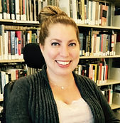 Image of a white woman sitting in front of a bookshelf. Her hair is in a bun and she is wearing a grey sweater. wheelchair headrest is visible.
