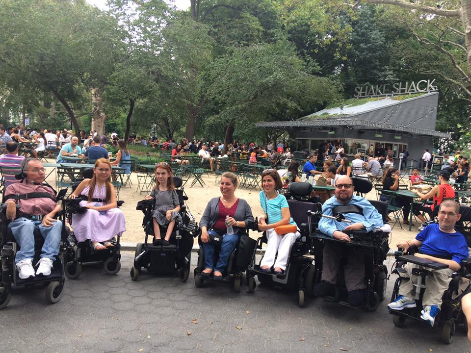 A gathering of seven members of NMD United in NYC. All members use power wheelchairs.