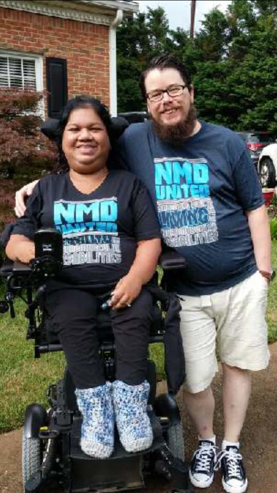 Woman elevated in her power wheelchair next to a bearded man standing. Both are wearing NMD United t