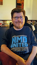 A man with reddish-brown hair and a beard is wearing glasses and smirks at the camera. He is sitting in a power wheelchair and wears a tee-shirt with a dark blue background and lighter blue text that reads: NMD United Connecting Adults Living with Neuromuscular Disabilities