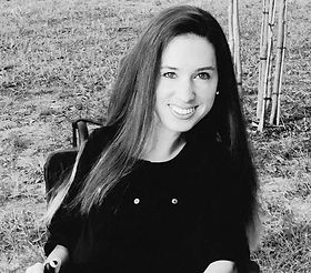 Black and white photo of Alex Landis. She is outside sitting in her wheelchair. Her long straight hair cascades over one shoulder. She is smiling very big and looking at the camera.