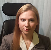 Close up photo of Kendra Scalia. She has long blonde hair and is smiling at the camera. She wears a cream colored blouse and a tan blazer on top. She is pictured sitting in her wheelchair.