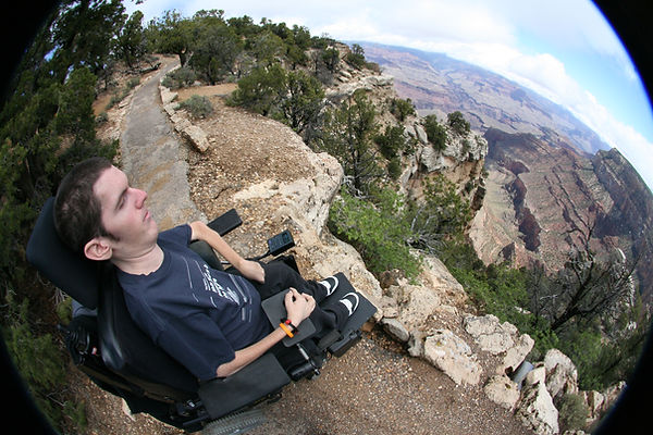 In a fish-eye lens, Danny gets as close to the dropping point of the Canyon as possible with his power wheelchair. The expression on his face is not scared at all, but peaceful and serious as the expansive views of the gorgeous Grand Canyon display themselves in front of him.