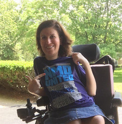 Woman sitting in her power wheelchair pointing at her shirt that says NMD United