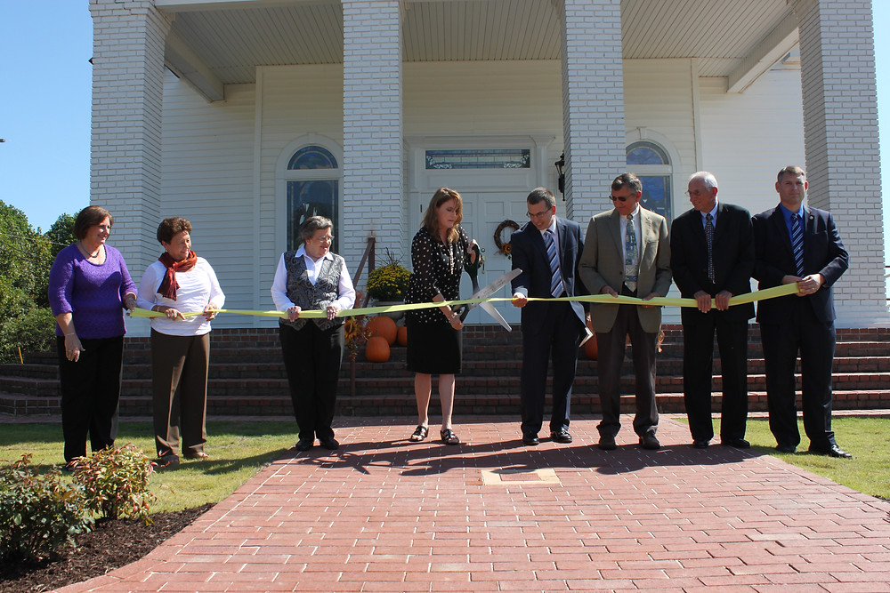 Members of the Bicentennial Committee cut the yellow ribbon for the new sidewalk