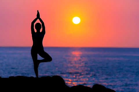 Woman's figure doing yoga on a seaside durig sunset
