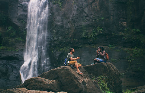 Pair talking next to a waterfall in the mountains