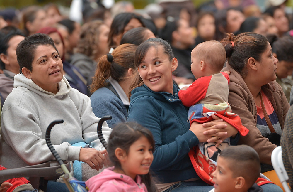 Woman with a child in her arms sitting in packed audience