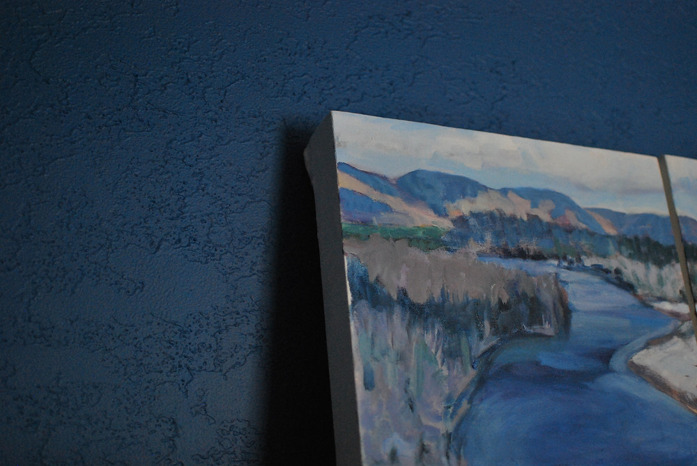My mother's painting of Margaree Valley against a freshly painted blue wall