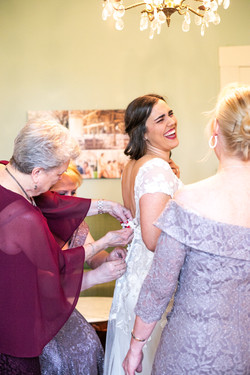 bride Taylor's mother figures helping her put on her dress