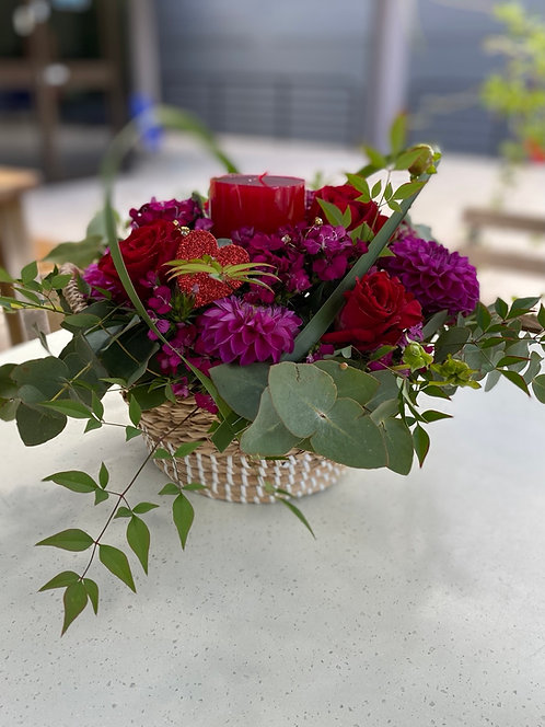 Basket of roses and pinks with red candle