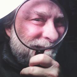 Jonny G looking through a magnifying