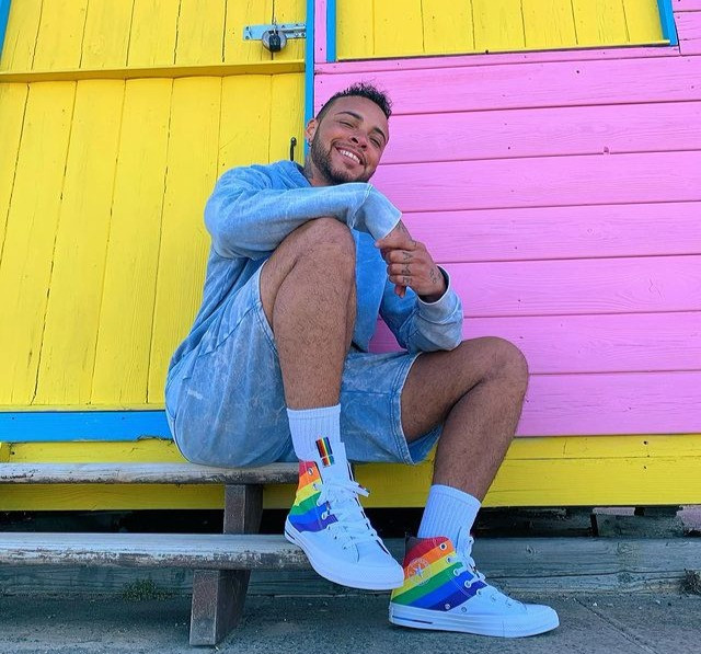 A photo of Kenny smiling at the camera, wearing Pride trainers and sat outside a colourful hut with bright yellow, pink and blue paint