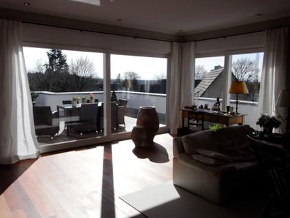 Lichtdurchflutetes Penthouse Wohnzimmer mit großzügigem Balkon