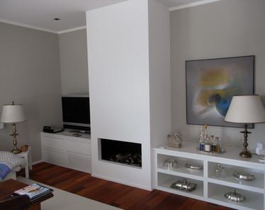 Wohnzimmer mit Kamin und maßgeschneiderten Einbaumöbeln