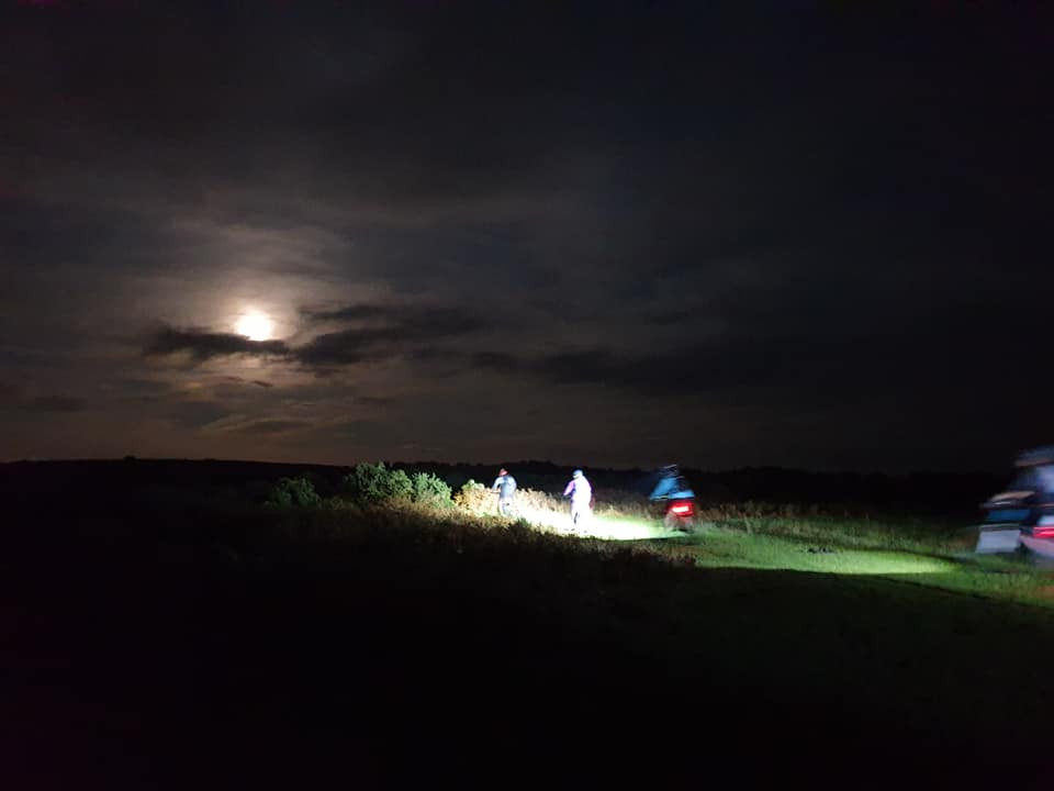 Four mountain bikers ride in the moonlight